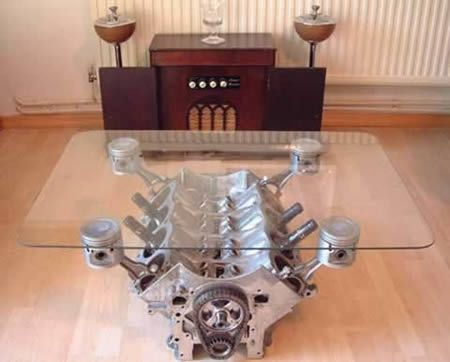 Aluminum engine block coffee table. Nice pistons raise up glass. This is actually pretty cheap and easy to make if you can find a good block at your local junkyard. The most expensive part is the tempered glass.