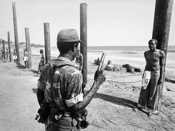 A Liberian army soldier stands ready to execute a former cabinet minister following the 1980 coup. The minister in the photo: Cecil Dennis. 1980