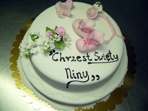 tort na chrzciny ozdoby na samej górze buciki dziecka wykonane z masy plastyczne