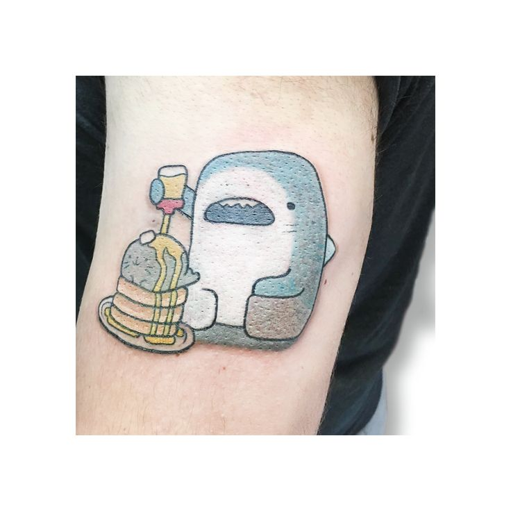 A cute color tattoo, shark eating seal pancakes.