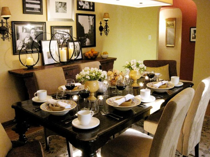 Designer Angelo Surmelis creates a warm and inviting space for entertaining with a soft yellow paint color on both the walls and ceiling. Enlarged black-and-white family photos add graphic punch while a dark-stained table and upholstered chairs create an elegant and comfortable place to linger over a home-cooked meal.