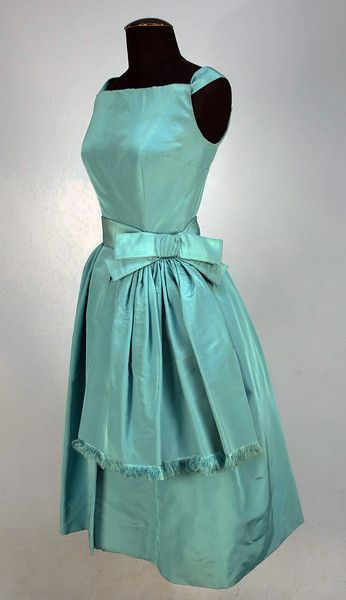 CHRISTIAN DIOR SILK COCKTAIL DRESS, 1950's. Sleeveless robin's egg blue faille with wide strap emanating from upper side of square cut bodice forming band along top of back, asymmetrical skirt with two wide center pleats shorter at left hip below wide self bow, side pockets, crinoline underskirt, back zipper.