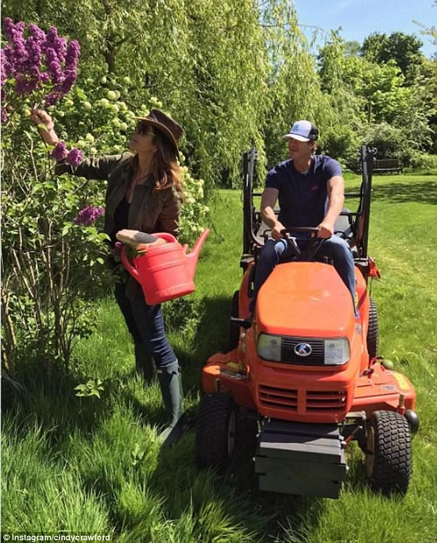 Hired help: Supposedly tending the lawns and plants at George and Amal Clooney's Berkshire home are ex-supermodel Cindy Crawford and her husband Rande