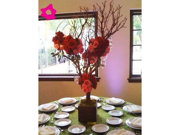 Centro de mesa com galho e flores vermelhas