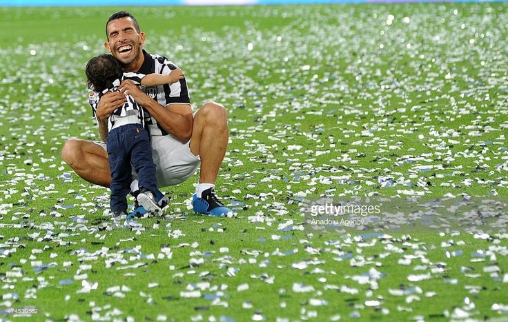 Juventus' forward from Argentina Carlos Tevez plays with his child at the end of a medal ceremony following the Italian Serie A football match Juventus vs Napoli on May 23, 2015 at the Juventus stadium in Turin.