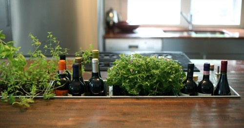 Or have a custom pan made to hold items like fresh herbs, wine, oil and vinegar in a kitchen island countertop. It's a great way to get things off of the counters, and even though they're in the counters, it creates a sense of calm through its intention. Organization is very psychological — it's about making things look as if they have a place or are meant to be there.