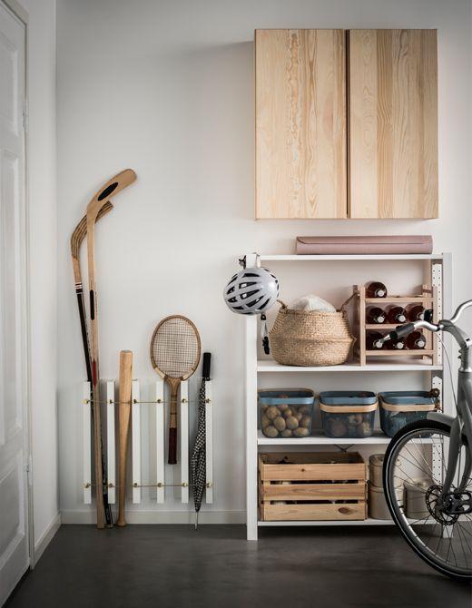 Idée de customisation d'étagères pour photos IKEA MOSSLANDA placées verticalement et servant de rangement aux raquettes de tennis, sticks de hockey, battes de baseball et parapluie.