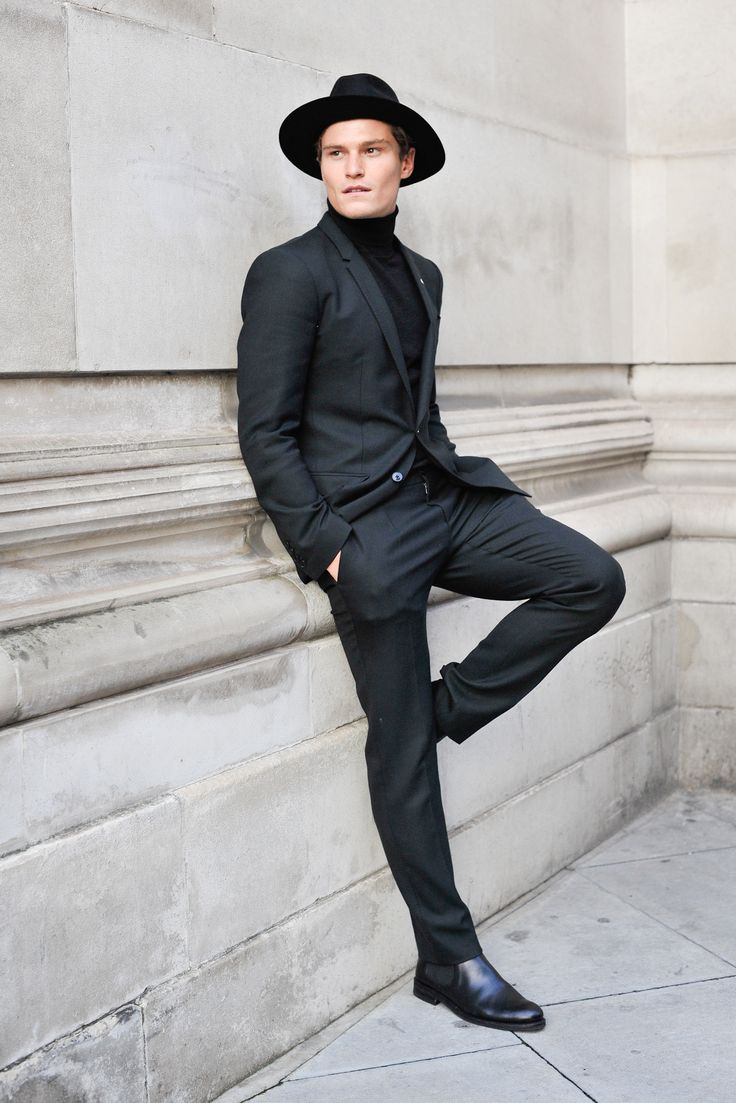 Shop this look on Lookastic:  https://lookastic.com/men/looks/black-suit-black-turtleneck-black-chelsea-boots/15320  — Black Wool Hat  — Black Turtleneck  — Black Suit  — Black Leather Chelsea Boots