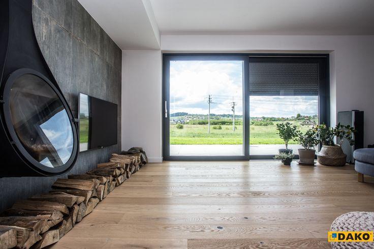 Szerokie drzwi przesuwne HST w nowoczesnym kolorze: szary antracyt pięknie komponują się z minimalistycznym wnętrzem i otwierają dom na zewnątrz