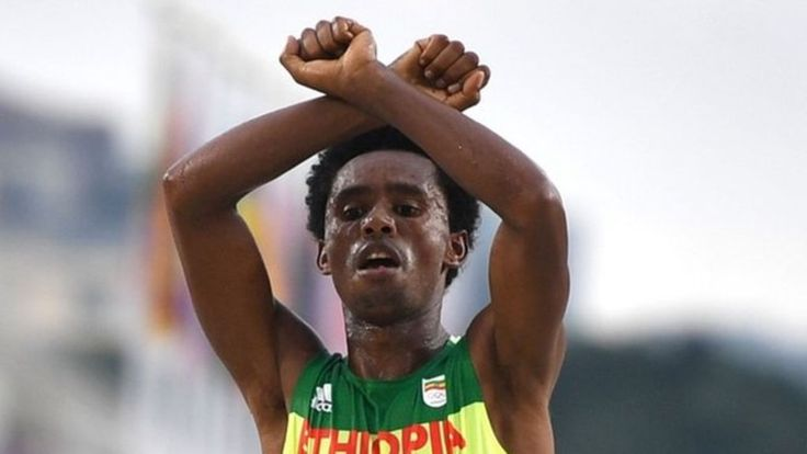 Feyisa Lilesa crosses his arms as he wins a silver medal - a gesture used by his Oromo people at home to protest against the government.