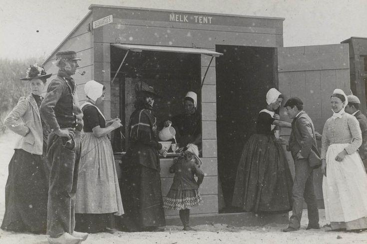 Mannen, vrouwen en een kind bij de melktent aan het strand te Domburg. Drie van de vrouwen zijn gekleed in Walcherse streekdracht. ca 1900