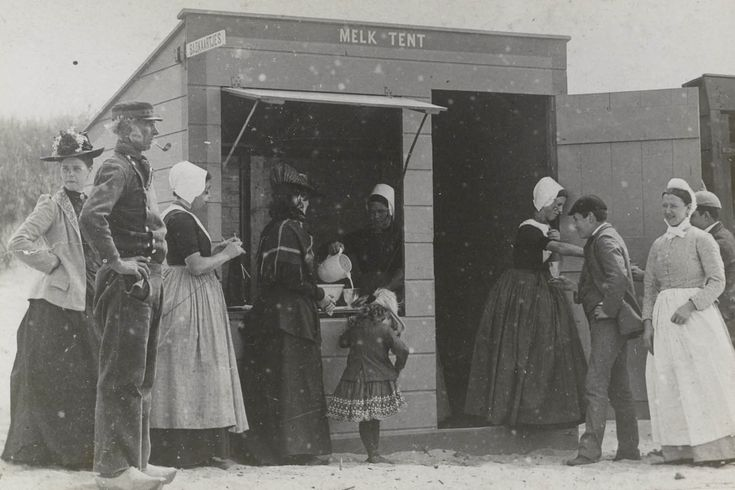 Mannen, vrouwen en een kind bij de melktent aan het strand te Domburg. Drie van de vrouwen zijn gekleed in Walcherse streekdracht. ca 1900 #Zeeland #Walcheren