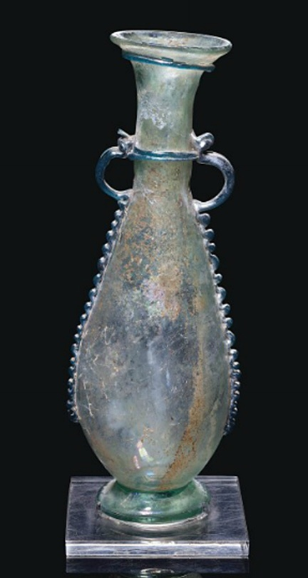 A LATE ROMAN OR BYZANTINE PALE GREEN GLASS AMPHORA   CIRCA 5TH CENTURY A.D.   Free-blown, the pear-shaped body on a disc foot, with long neck and everted rim, with applied turquoise glass zigzag trails down the sides of the body, twin looped handle, and collar around neck and under rim