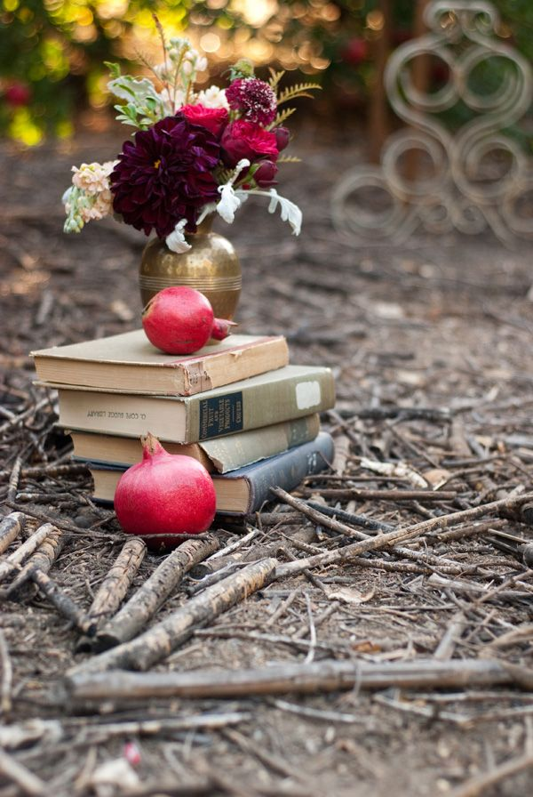 Pomegranates and books in the forest. Absolutely beautiful. It just looks like it has a story.