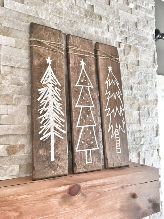 These Rustic Wooden Christmas Trees are a unique piece for your home during the holiday season! This listing is for a set of three hand painted white Christmas trees on walnut stained wood pieces and two pieces are sprinkled with gold glitter for a little sparkle :) The wood has been sanded smooth, stained, painted & distressed by hand for that perfect rustic touch Measurements: each piece of wood is 24 x 5.5 Each wooden tree has a brass plated tooth hanger on the back for easy hanging! ...