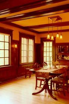 The Nicolai-Cake-Olson House 1905-1906. Craftsman style lighting from Rejuvenation House Parts casts a warm glow in the fir paneled dining room.  Though abundant, the woodwork shapes are utterly simple.