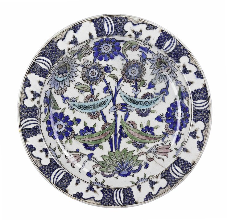 Dish, polychrome underglaze painted pottery with a symmetrical floral design and with a rock and wave motif on the rim, based on the design of a 16th century dish from Iznik: Middle East, Iran, probably Isfahan, c1897.