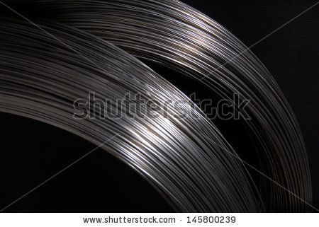 Steel wire in a coils on the dark background - stock photo