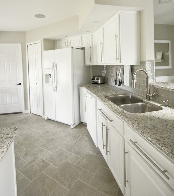 Kitchen with white appliances. Love the grey floor and the glass subway tile backsplash
