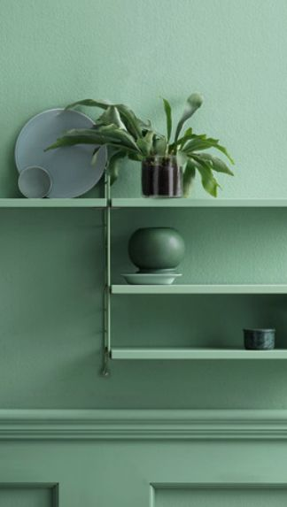 The String Pocket shelving system in green consists of two side panels and three shelves.