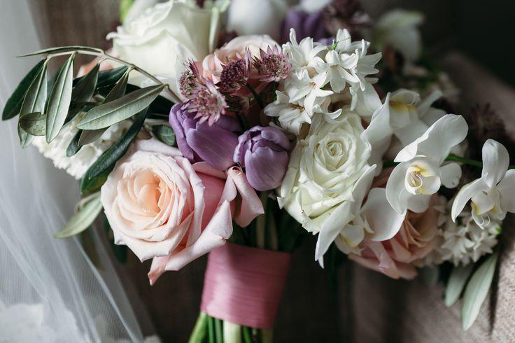 Нежный букет невесты из тюльпанов, гиацинтов, роз и орхидей, дополненный изящной ветвью оливы.
