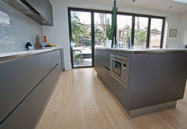 Anthracite grey laminate island kitchen design with low level microwave to save on worktop space, and bi-fold doors to allow a flooding of light within the kitchen.