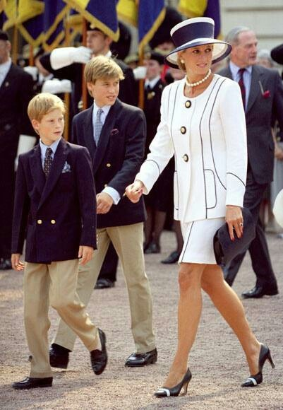 White jacket and skirt with blue piping and coordinating hat. Love the hat, absolutely stylish even today. Princess Diana, and Prince Harry and Prince William.