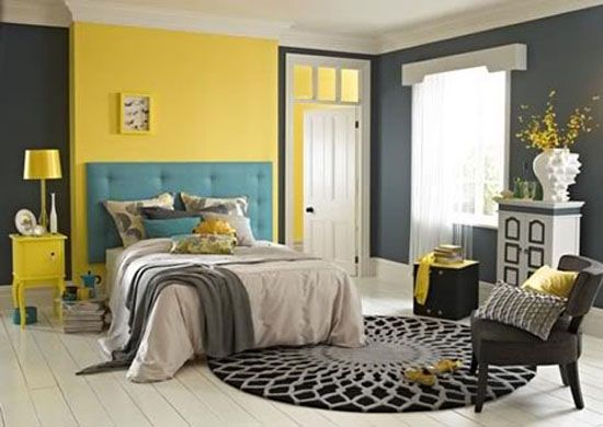 Chambre gris et jaune avec un immense tapis graphique au sol.