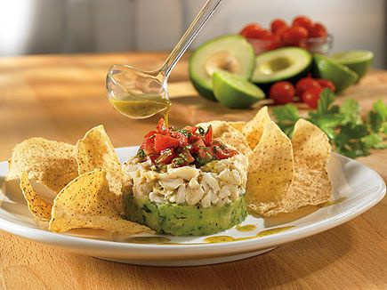 Crab & Avocado Stack: Fresh avocado and marinated crab meat topped with minced tomato basil and a drizzle of wasabi vinaigrette. Served with white corn tortilla chips.     At Outback Steakhouse