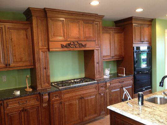 I absolutely love how these dark-stained cabinets in this kitchen look against the green walls. I've heard that cabinets like these can increase the value of your home by up to 5%. I'll have to keep this idea in mind as my wife and I get ready to remodel our home and put new cabinets in.