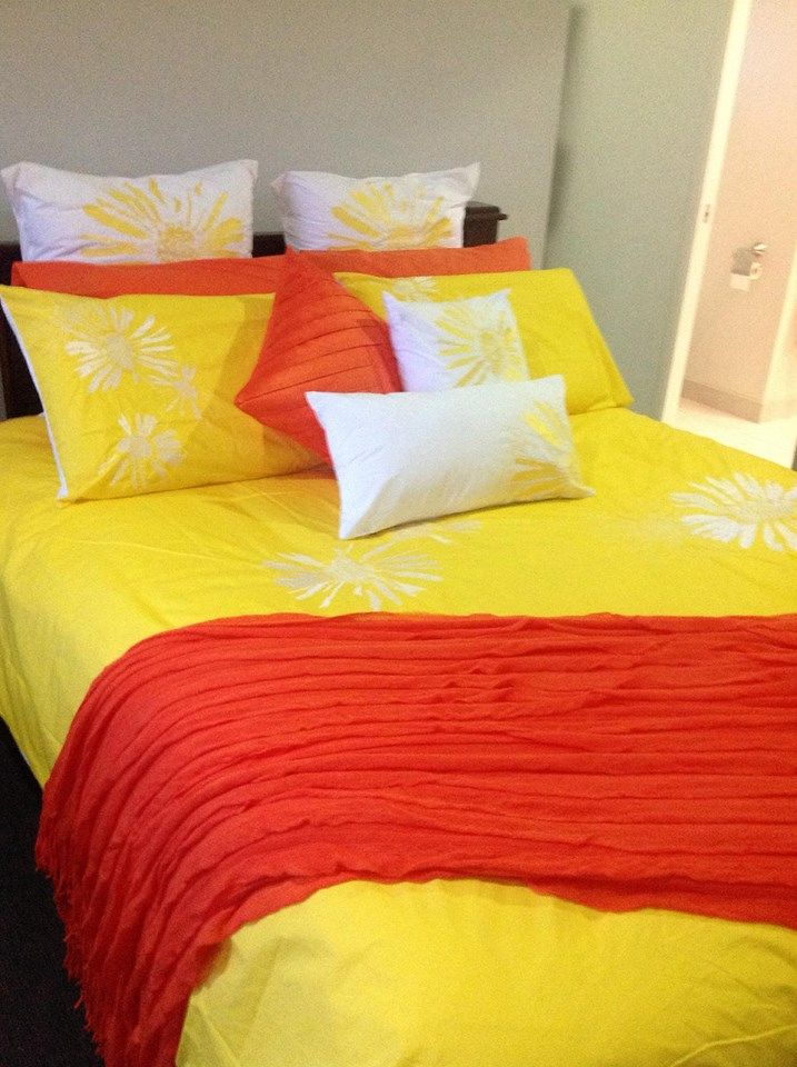 Catalina Yellow from Lorraine Lea Linen on customer Maria's bed. Maria has teamed Catalina with orange accessories. Image thanks to consultant Amanda Radford