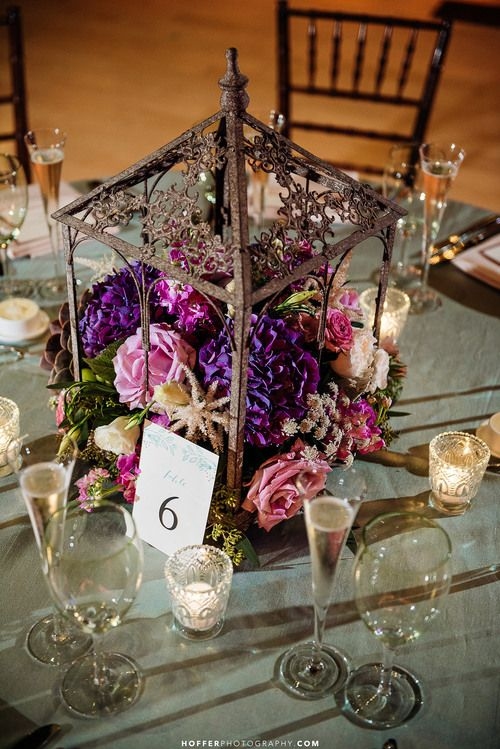 Rustic iron terrarium lantern centerpieces with antique votives. Wedding flowers in lavender, white, purple, pink and blue. Floral Design: www.papertini.com Photography: www.hofferphotography.com