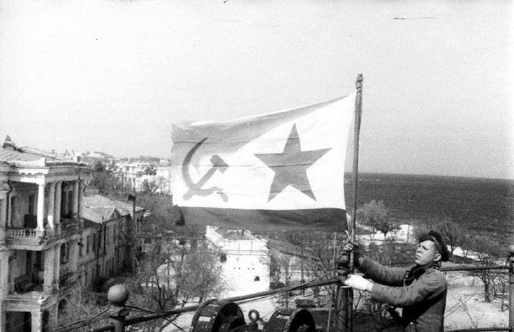 Морской пехотинец устанавливает советский военно-морской флаг в освобожденном Севастополе. Май 1944