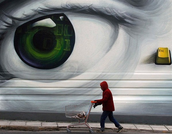 """""""An immigrant pushes an empty shopping trolley in a poor Athens neighbourhood."""""""