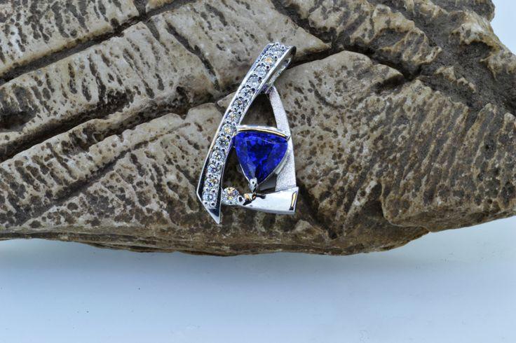 A beautiful custom piece of white gold, blue saphire stone and white diamonds.  www.winnipegcustomjeweler.com