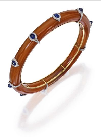 Platinum, Gold, Agate, Sapphire and Diamond Bangle-Bracelet, France:  The carved agate bangle-bracelet decorated with ten sugarloaf cabochon sapphires measuring approximately 4.5 by 3.5 by 2.5 mm, accented by rose-cut diamonds, internal circumference 8½ inches, with French assay mark; circa 1920.