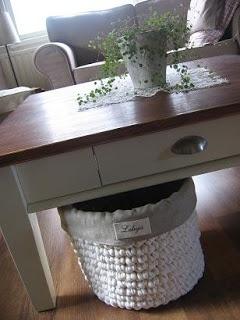 Gran cesta de trapillo, forrada con tela de algodón, ideal como papelera en un estudio.