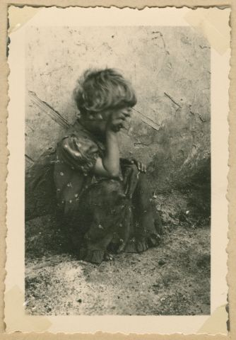 A young Jewish girl with her hand obscuring her face sits outside in Deblin-Irena.