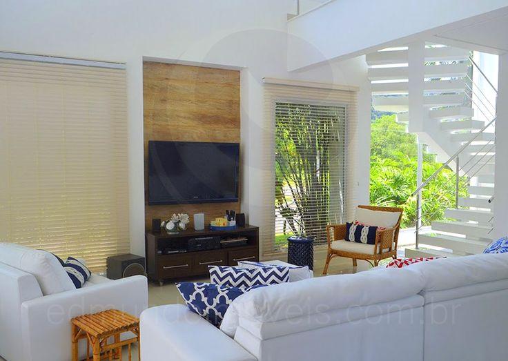 No living, confortáveis sofás em couro branco foram dispostos em frente à telinha para as sessões de filmes e seriados. Almofadas em tons de vermelho e azul dão um toque colorido e bem humorado à sala.