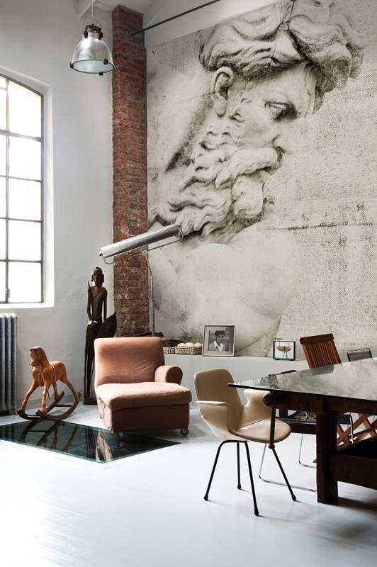 """W tym surowym, pofabrycznym wnętrzu dominuje przedstawienie kamiennej, starej rzeźby. Reszta to konwencjonalne, eleganckie sprzęty, które jednak w towarzystwie przeskalowanej twarzy z kamienia nabierają innego charakteru. Pozostawiono fragment ceglanej ściany i oryginalną stolarkę okienną oraz kaloryfer, żeby salon nie wydawał się zbyt """"salonowy""""."""