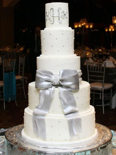 silver and white wedding | Round white 5 tier wedding cake with large silver bow and monogram on ...