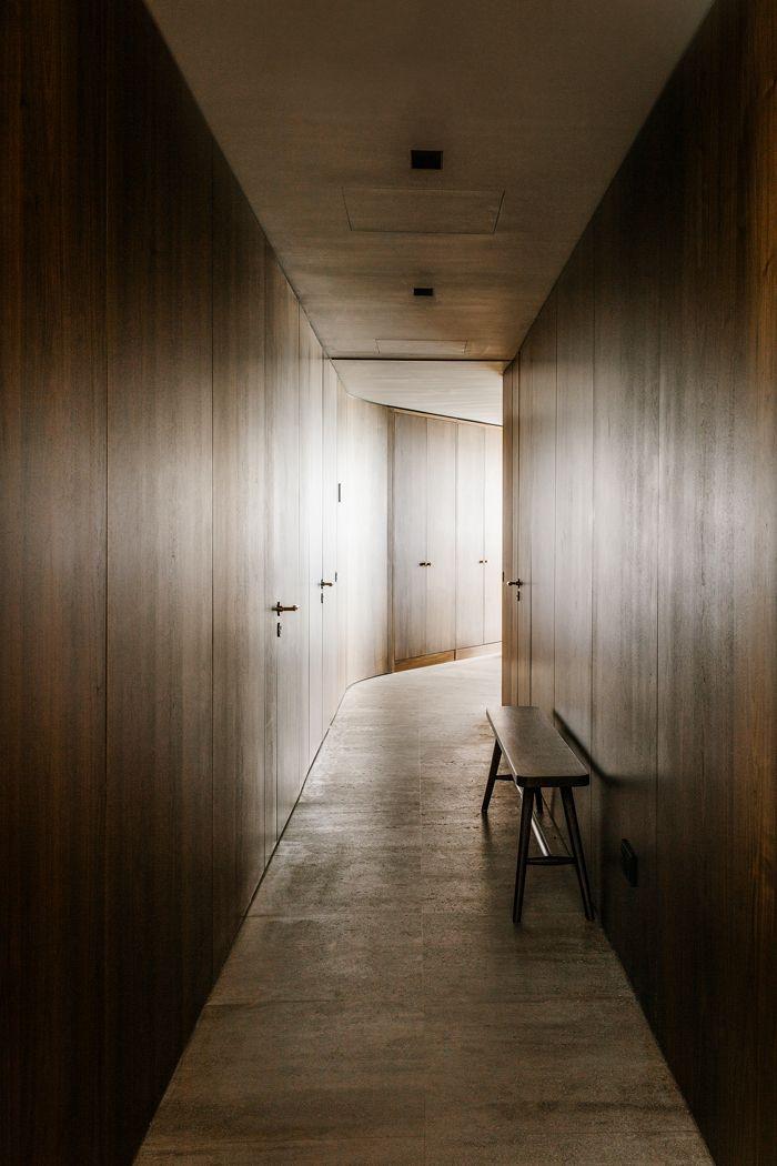 Dans le couloir, les panneaux en noyer d'Amérique sont omniprésents, reliant les pièces à vivre et laissant apercevoir la lumière qui baigne l'Embassy House.