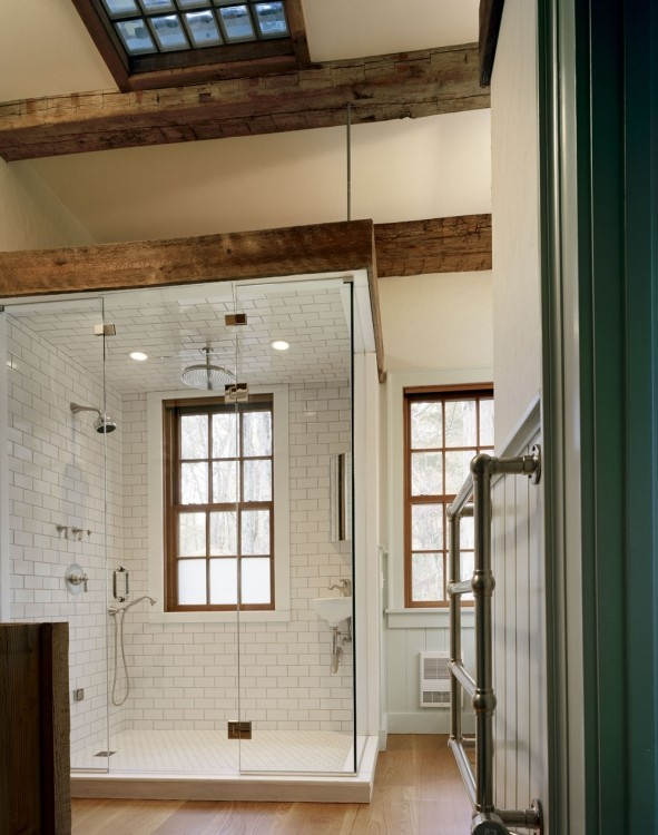 Tile in the shower is in the shape of brick, which fits the motif of this restored old barn.  Cool hardware hanging on wall for towels.