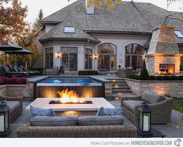 A small pool with fountain looks great lit up by the fire pit in front. So pretty!
