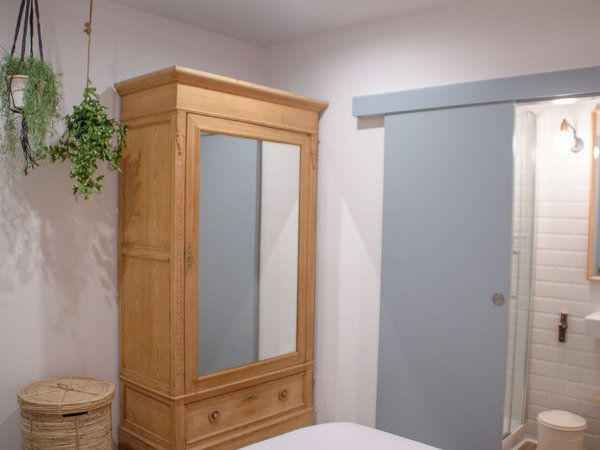 Dormitorio con baño integrado y armario exento en madera