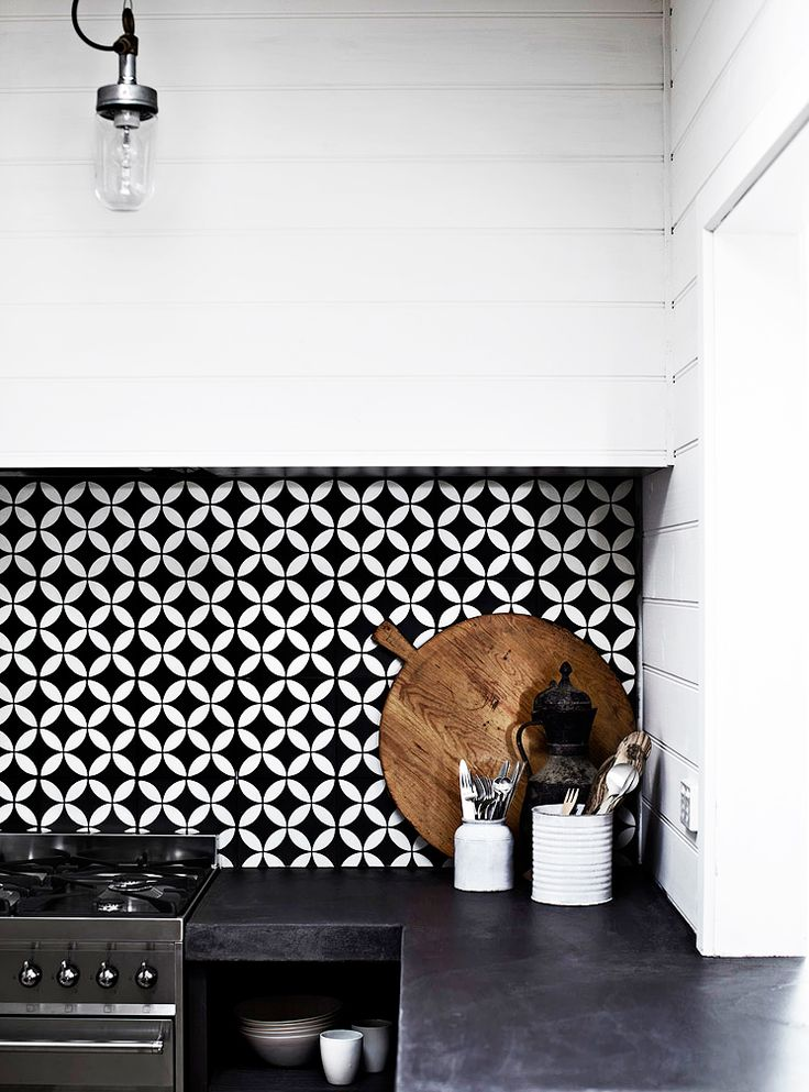 Black and white kitchen backsplash with dark wood cutting board