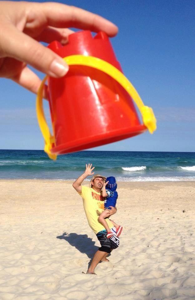 Padre protegiendo a su hijo de un cubo gigante. Fotografía divertida en la playa