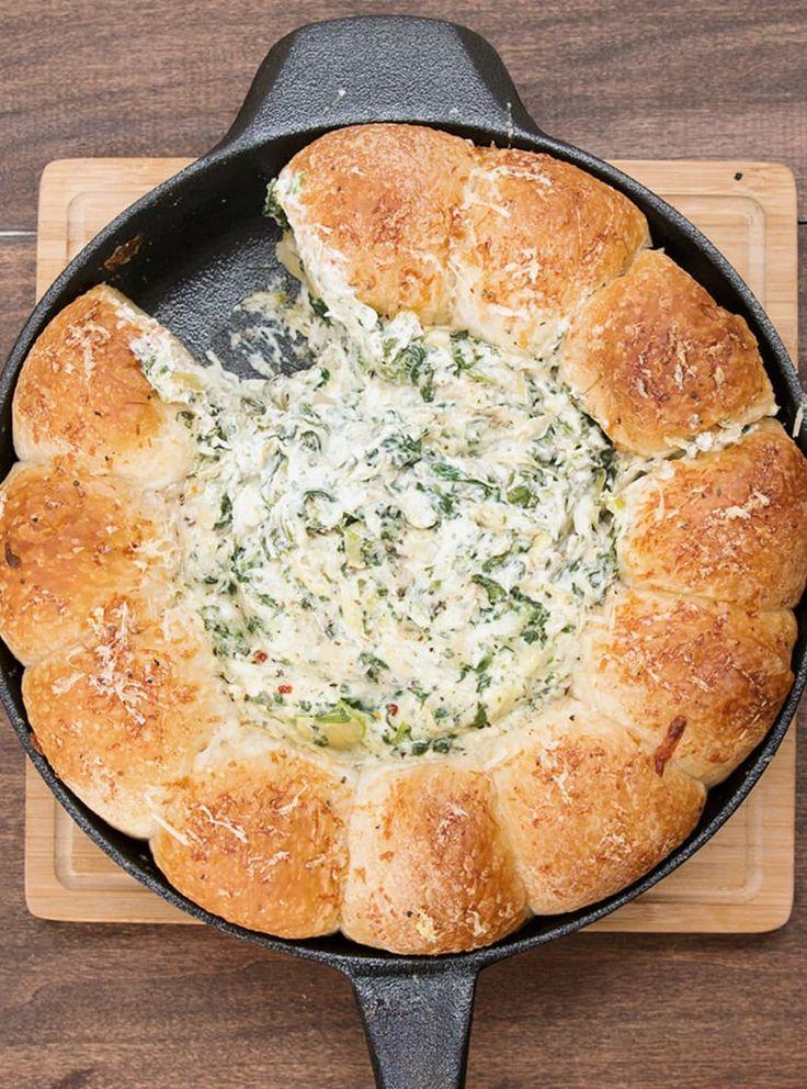 Esto es lo que necesitas:* 12 bolas de masa congelada * 8 oz de queso crema, suave * 1/2 taza de queso parmesano rayado* 1/2 taza de queso romano rayado* 1/2 taza de queso mozzarella rayado* 1/4 taza de crema agria* 1 14-oz de corazones de alcachofas (1 1/2 taza) en lata, escurridos y picados* 3/4 tazas de espinaca congelada picada, deshilada y escurrida* 2 dientes de ajo, picados* 1 cucharada de albahaca* 1/2 cucharada de hojuelas de pimiento rojo * Aceite de oliva Instrucciones:Cubre con…