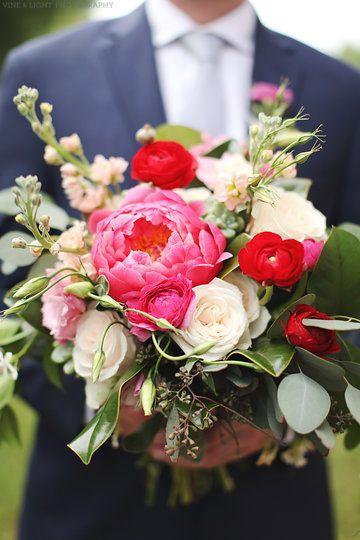 loose unstructured bridesmaid bouquet of coral charm peony, red ranunculus, Vendala roses, hot pink ranunculus, light pink lisianthus, jasmine vine, magnolia leaves, lemon leaf, peach stock, succulents & seeded eucalyptus wrapped in cream muslin ribbon.