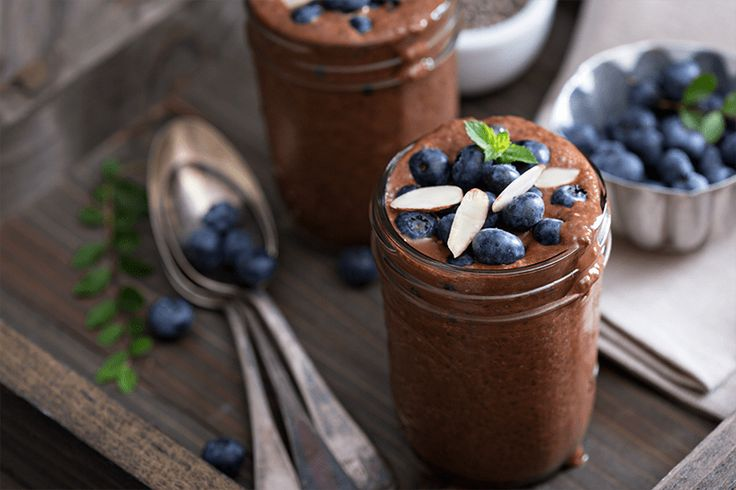 Two glasses of vegan avocado chocolate mousse topped with blueberries
